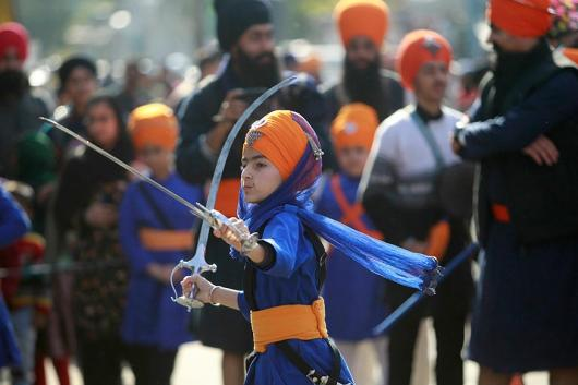 An Indian Sikh girl displays traditional martial art skills during a religious procession ahead of the birth anniversary of Guru Gobind Singh in Jammu. The birth anniversary of Guru Gobind Singh, the tenth Sikh guru, will be marked on January 5. (Image: AP)