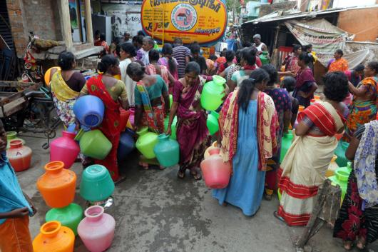 People stand in queues to fill vessels filled with drinking water from a water tanker in Chennai. (Image: AP)
