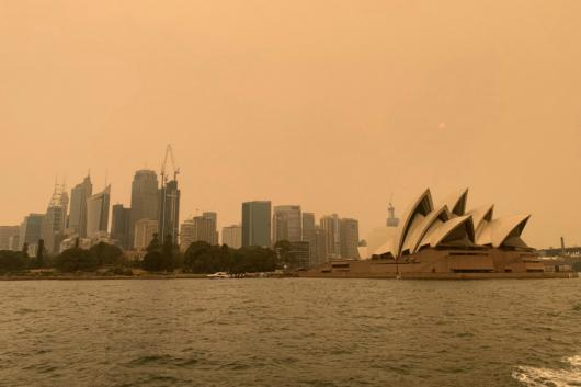 The haze from bushfires obscures the sun above the Sydney Opera House in Sydney on Friday. (Reuters)