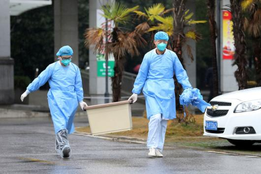 Medical staff carry a box as they walk at the Jinyintan hospital where the patients with pneumonia caused by the new strain of coronavirus are being treated in Wuhan Hubei province China