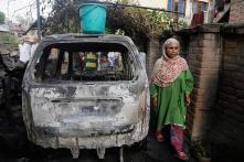 Kashmiri Villagers Inspect Houses Damaged in Redwani Gun Battle