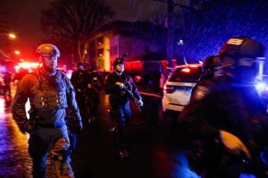 Law enforcement personnel walk near the scene following a shooting, Tuesday, December 10, 2019, in Jersey City, NJ (AP Photo/Eduardo Munoz Alvarez)