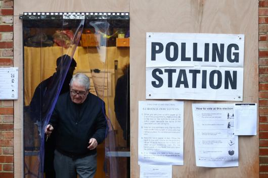 An elder leaves the garage of a residential house, converted to a poling station, to vote in the general election in South Croydon, in London. (Image : Reuters)