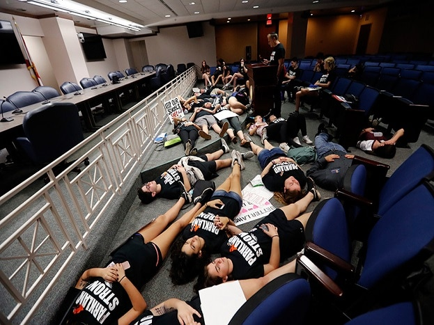 Seventeen student survivors from Marjory Stoneman Douglas High School lie down on the floor in silence and pray at the approximate time of the attack one week ago, inside the state capitol, in Tallahassee. (Image: AP)