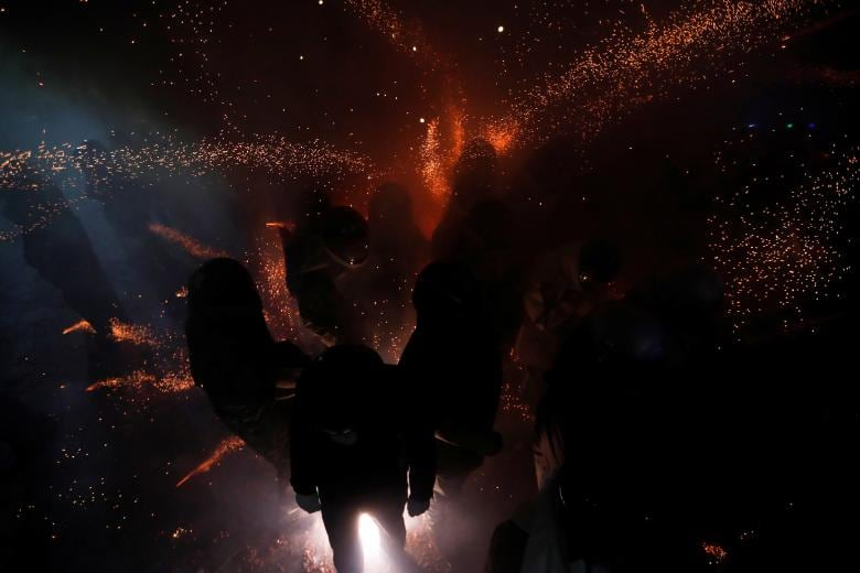 Participants wearing motorcycle helmets get sprayed with firecrackers, during the 'Beehive Firecrackers' festival at the Yanshui district in Tainan, Taiwan. (Image: REUTERS)