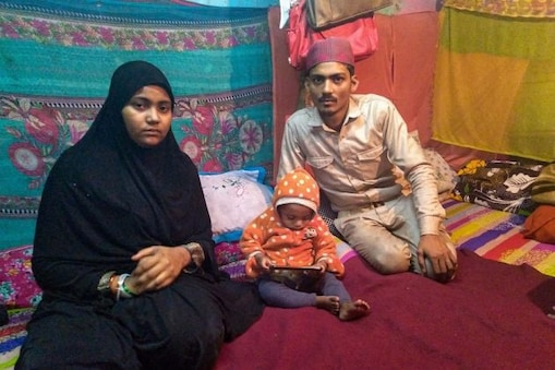 Mohammed Arif (R) and Nazia with one of their surviving children pose for photographs at their residence in Batla House, New Delhi, Monday, Feb. 3, 2020. Arif and Nazia's infant son, whom they used to take to the Shaheen Bagh protests, reportedly died due to cold. (Image: PTI)