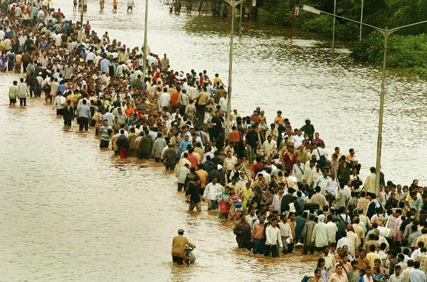 વરસાદના પાણી વચ્ચેથી પસાર થઈ રહેલા લોકો.(એએફપી તસવીર)