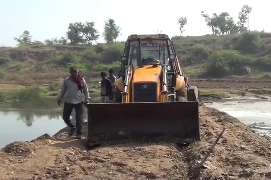 જેસીબીની મદદથી નદી વચ્ચે ડીપની કામગીરી થઇ રહી છે.