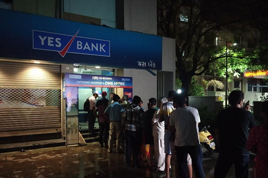 રુત્વિજ સોની, અમદાવાદ/નવી દિલ્હી : ભારે વિત્તીય સંકટથી ઝઝુમી રહેલા પ્રાઇવેટ સેક્ટરની યસ બેંક (Yes Bank)પર RBIએ પ્રતિબંધ લગાવી દીધો છે. RBIના આ પ્રતિબંધ પછી કોઈપણ ખાતાધારક પોતાના એકાઉન્ટમાંથી 50 હજાર રુપિયાથી વધારે રકમ ઉપાડી શકશે નહીં. રિઝર્વ બેન્કે સરકાર સાથે વિચાર-વિમર્શ કર્યા પછી બેંકના નિર્દેશક મંડળને ભંગ કરતા આ નિર્ણય કર્યો છે. આ નિર્ણયના કારણે અમદાવાદમાં મોડી રાત્રે બેેંકના એટીએમની બહાર લાંબી કતારો જોવા મળી હતી. બીજી તરફ રાજકોટના રેસકોર્સ ખાતે આવેલી યસ બેંકમાં પણ પૈસા ઉપાડવા માટે લોકોની લાઈનો લાગી છે. લોકો એટીએમમાંથી પૈસા ઉપાડી રહ્યા છે. જેમ જેમ લોકોને ખબર પડી રહી છે તેમ તેમ લોકો એટીએમ પર પહોંચી રહ્યા છે