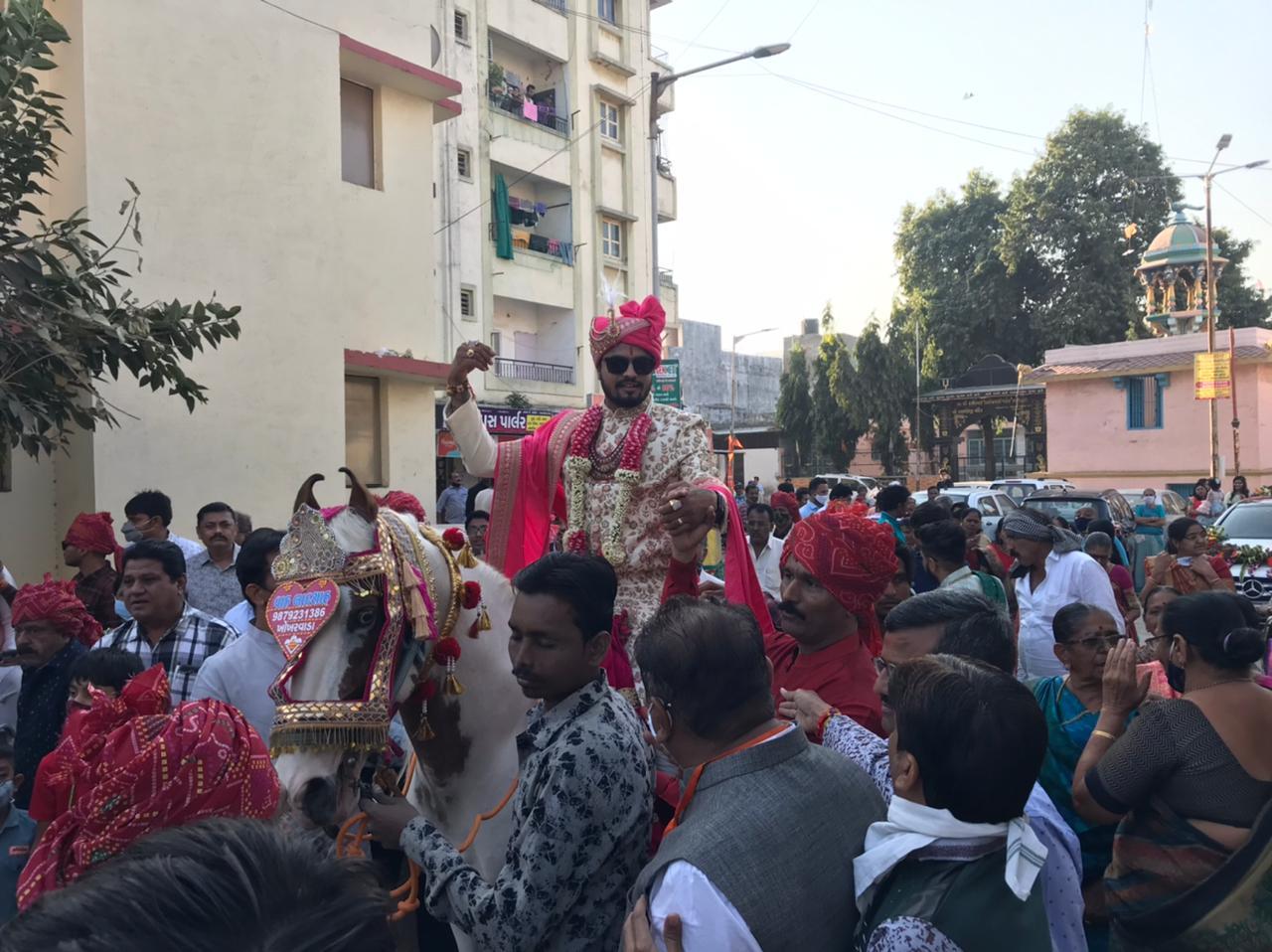પ્રણવ પટેલ, અમદાવાદ: અમદાવાદમાં (Ahmedabad) સહિત છ મહાનગરપાલિકામાં (Mahanagarpalika) આજે મતદાન (Election) થઇ રહ્યું છે. ત્યારે લોકોમાં પણ ઉત્સાહ દેખાઇ રહ્યો છે. શહેરના થલતેજ ગામમાં રહેતા બારોટ પરિવારના પુત્રનું આજે લગ્ન (marriage) છે. પરિવારની જાન હિંમતનગર જવાની છે તે પહેલા પરિવારે પોતાનો લોકશાહીનો પર્વ ઉજવીને મતદાન કર્યું છે. વરરાજા (groom) ધનરાજ બારોટ ઘોડે ચઢીને મતદાન કરવા પહોંચ્યા હતા.