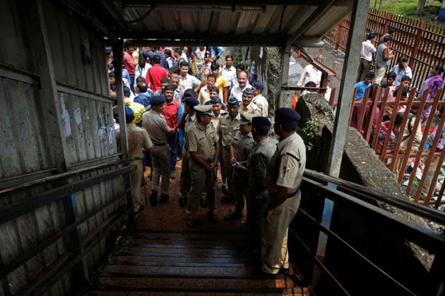 Policemen inspect the site of a stampede at a railway station's pedestrian overbridge in Mumbai
