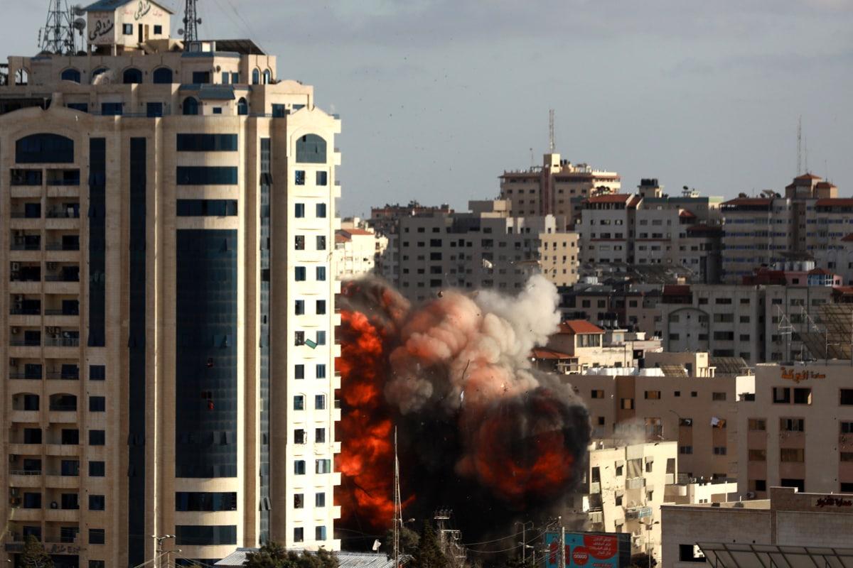 غزہ میں اسرائیلی فضائی حملہ کے بعد ایک عمارت سے آگ کے شعلے اور دھنویں اٹھتے ہوئے ۔ (AP Photo/Hatem Moussa)
