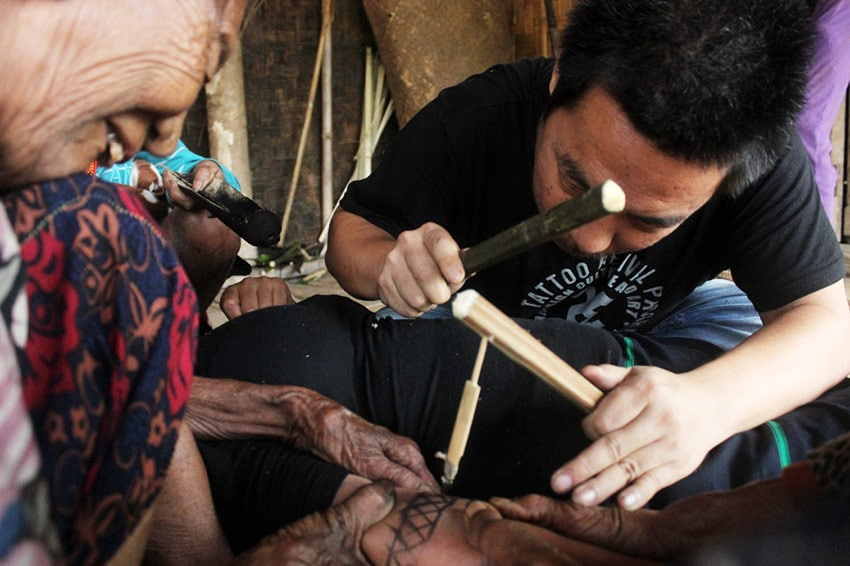 Tattooing in traditional style with a Konyak Tattooing Queen