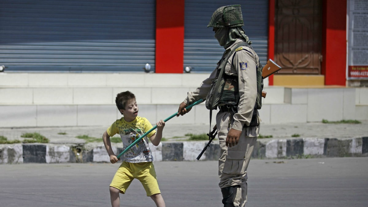 A boy playing with a soldier in downtown Srinagar. (Abid Bhat - August, 2017)