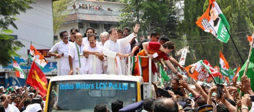 பிரசார வேனில் வரும்போது தொண்டர்களுக்கு கை கொடுத்த பிரியங்கா காந்தி. (Image: UPCC)