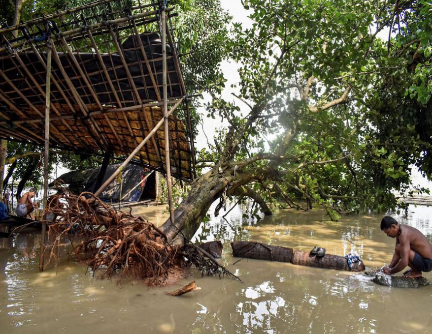 கவுகாதியில் வெள்ள நீரில் தனது துணிகளை துவைக்கும் ஒருவர். (Image: AP)