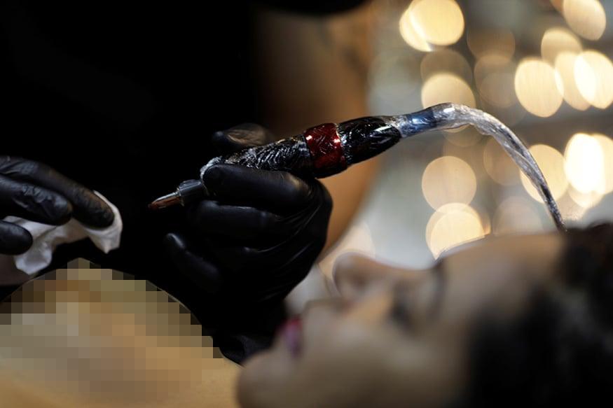 2. బ్రెజిల్లోని రియో డి జనీరోలో ఆర్టిస్ట్ యుర్గన్ బ్యారెట్తో టాటూ వేయించుకుంటున్న బ్రెస్ట్ క్యాన్సర్ పేషెంట్. (Image: Reuters)