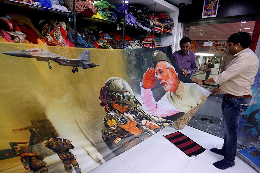 7. సూరత్లోని ఓ షాపులో ఇండియన్ ఆర్మీ, భారత ప్రధాని నరేంద్ర మోదీ చిత్రాలతో ఉన్న చీరను చూపిస్తున్న సిబ్బంది. (Image: Reuters)